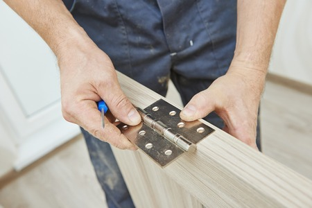 Close-up carpenter process of wood door hinge installation.