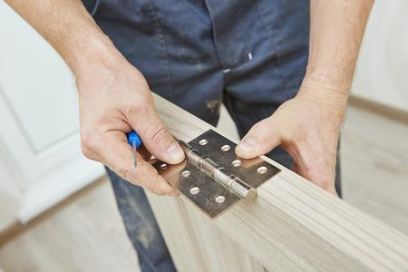 Close-up carpenter process of wood door hinge installation.