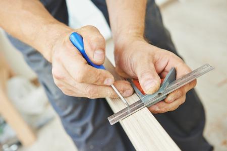 locksmith: Close-up carpenter process of wood door marking for locksmith installation