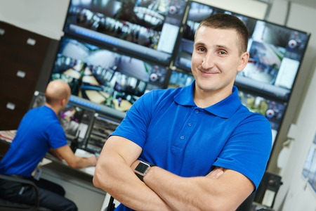 video surveillance: security executive chief in front of video monitoring surveillance security system