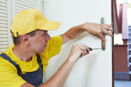 Homme travailleur bricoleur charpentier à intérieur en bois porte l'installation de serrure ou de la réparation Banque d'images