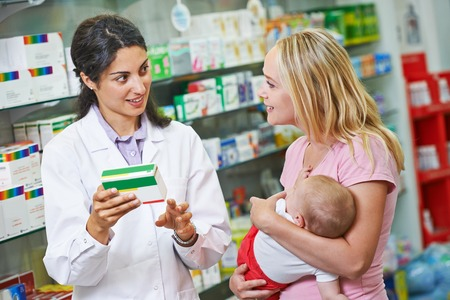 Cheerful pharmacist chemist woman giving vitamins to child girl in pharmacy drugstore Stock fotó
