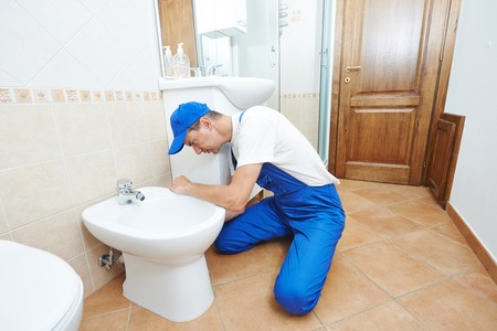 plumber worker working with spanner at sanitary washbasin installation system