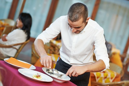 young male waiter prepairing fish food on tray serving at restaurant photo