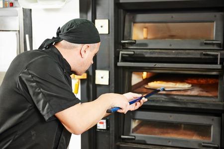 haciendo pan: panadero del cocinero en la toma de pizza uniforme en el restaurante estufa de la cocina