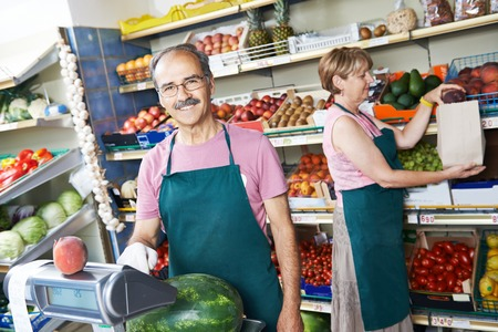 seller: adult senior sale man with assistant in fruit vegetable market shopping store Stock Photo