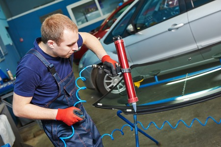 glasscutter: Automobile glazier adding glue on windscreen or windshield of a car in auto service station garage before installation Stock Photo