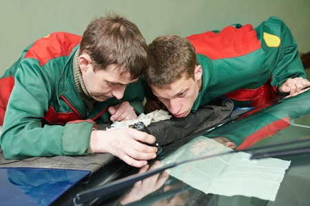 glasscutter: Automobile glazier repairman teaching or discussing with partner windscreen repair of a car in auto service station garage