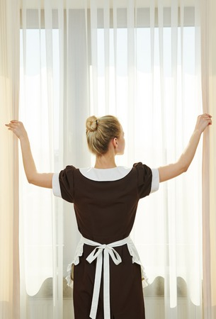 Hotel service. female housekeeping chambermaid worker with opening curtains of window in room