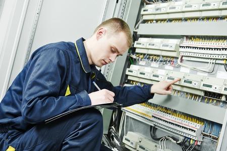 electrician engineer worker inspector  in front of fuseboard equipment in room photo