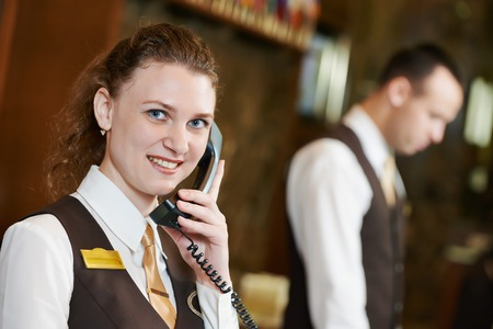 receptionist: Happy female receptionist worker with phone standing at hotel counter Stock Photo