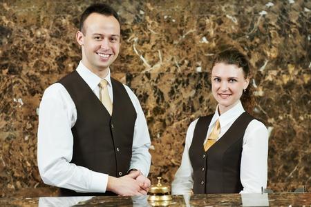 Recepční nebo recepční pracovníci stojící u hotelu přepážce