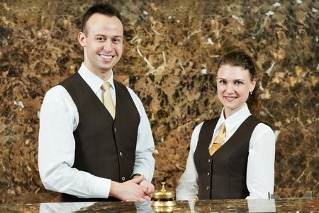 Receptionist or concierge workers standing at hotel counter Stock Photo