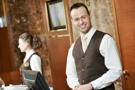 Happy receptionist worker standing at hotel counter Stock Photo