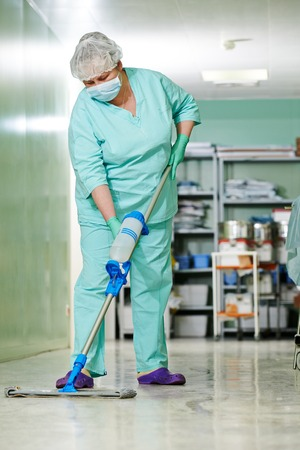 Adult cleaner maid woman with mop and uniform cleaning corridor pass floor of pharmacy industry factory or medical clinic
