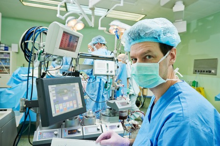 cardiac care: Surgery assistant nperfusionist with artificial cardiac valve at operation in cardiology clinic Stock Photo