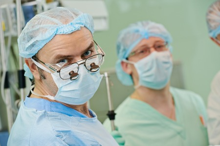 cardiosurgery: surgeons in uniform perform heart transplantation operation on a patient at cardiac surgery clinic