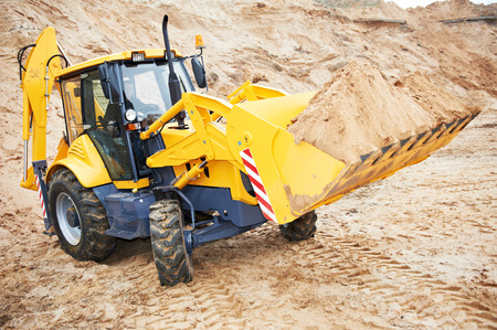 wheel loader: Wheel loader excavator with backhoe unloading sand at eathmoving works in construction site quarry Stock Photo