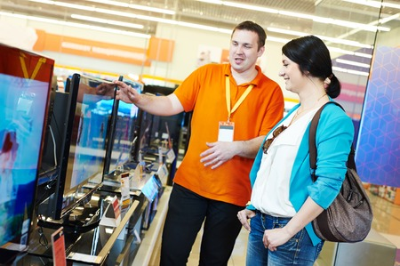 Young woman choosing tv set with shop assistant in home appliance shopping mall supermarket Stockfoto
