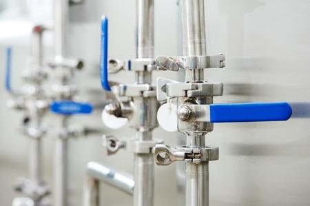 パイプと産業薬局工場のボイラー室における暖房設備の蛇口のバルブのクローズ アップ。浅い自由度