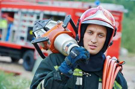 firefighter in uniform in front of fire engine machine and fireman team