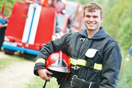 motor ardiendo: joven bombero sonriente en uniforme en el frente de la m�quina de bomberos Foto de archivo