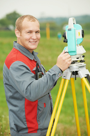 One surveyor worker working with theodolite transit equipment at spring field construction site outdoors photo