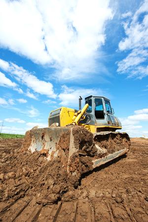 sand quarry: track-type loader bulldozer excavator machine doing earthmoving work at sand quarry