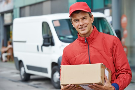 delivery truck: Smiling male postal delivery courier man outdoors  in front of cargo van delivering package
