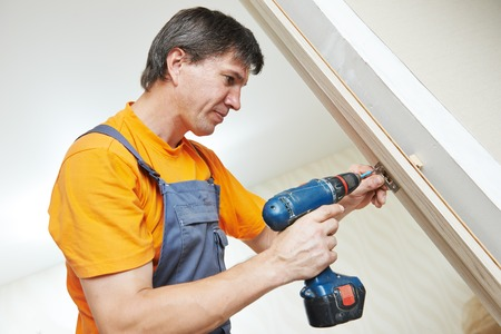 Male handyman carpenter at interior wood door lock installation Banco de Imagens - 31179287