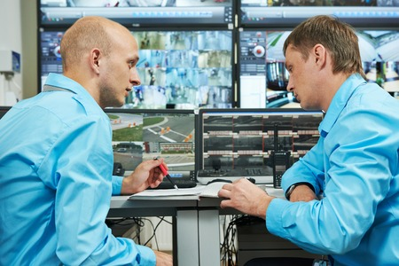 security room: two security guards watching video monitoring surveillance security system