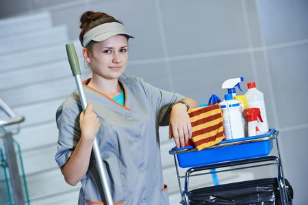 charwoman: portrait of female cleaner in uniform with mop and cleaning equipment