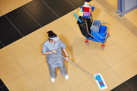 mujeres trabajando: limpieza de discos femenino con un trapeador y una limpieza uniforme piso pasillo del edificio de negocios p�blicos Foto de archivo