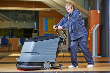 Floor care and cleaning services with washing machine in business centre hall