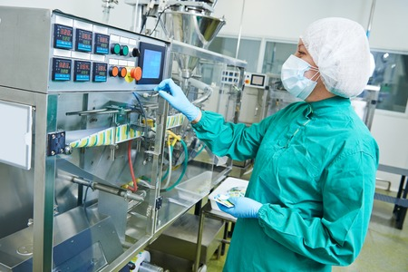 medicines: pharmaceutical factory woman worker operating production line at pharmacy industry manufacture factory Stock Photo