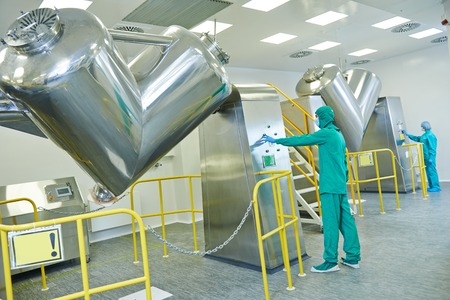chemical engineering: pharmaceutical factory workers operating powder mixer machine on production line in pharmacy industry manufacture factory