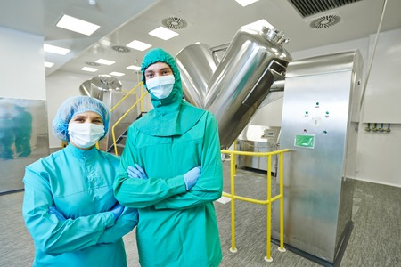pharmaceutical factory workers in front of powder mixer machine during tablet production at pharmacy industry manufacture factory