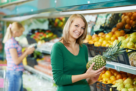 woman choosing pineapple during shopping at fruit vegetable supermarket photo