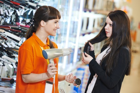 Young woman choosing electric hairdryer in home appliance shopping mall supermarket photo