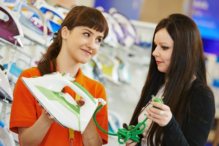 Young woman choosing electric iron in home appliance shopping mall supermarket photo