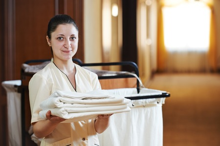 ホテルのルーム サービス。カートで寝具リネンと女性家事労働者