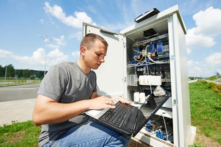 fettler: Ingeniero que trabaja con la computadora port�til al aire libre ajuste de equipos de comunicaci�n en la caja de distribuci�n