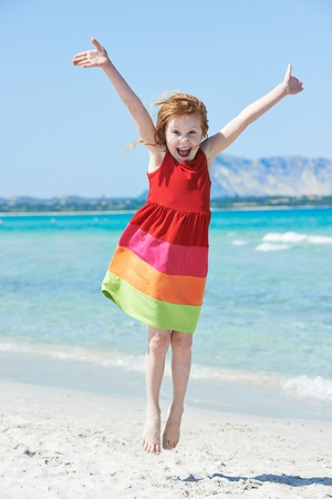 plage: laughing little girl jumping and have fun at summer sea beach