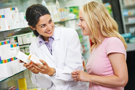 Cheerful pharmacist chemist woman suggesting vitamins female customer in pharmacy drugstore