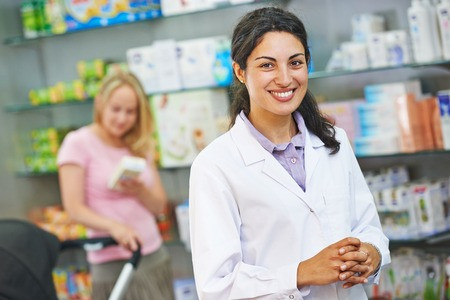 pharmacist: portrait of cheerful pharmacist chemist woman in pharmacy drugstore