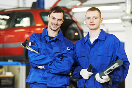 scheduled replacement: repairman mechanic workers at car engine auto repair shop service station