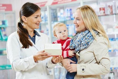 Cheerful pharmacist chemist woman giving vitamins to child girl in pharmacy drugstore Foto de archivo