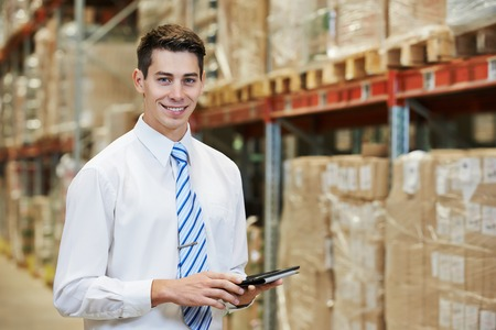 smiling manager in warehouse with tablet pc computer Фото со стока