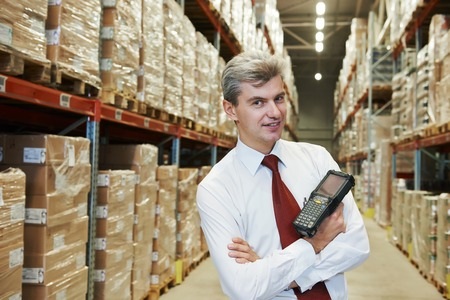 shipping order: smiling manager in warehouse with bar code scanner Stock Photo