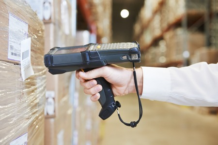 codigo de barras: trabajador mano paquete de exploración hombre con escáner de código de barras almacén en almacén moderno Foto de archivo